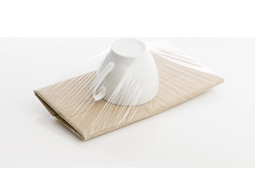 Buffer/insert gemaakt van op golfkarton gelijmd folie die het product stevig op zijn plaats houdt